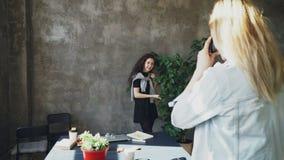 Het aantrekkelijke meisje stelt met grote installatie terwijl vrouwelijke collega die haar photogrpahing op digitale camera in mo stock footage