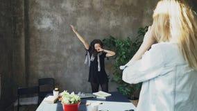 Het aantrekkelijke meisje stelt met grote installatie terwijl vrouwelijke collega die haar photogrpahing op digitale camera in mo stock videobeelden