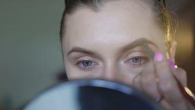 Het aantrekkelijke meisje van toepassing zijn maakt omhoog op haar brows 4K stock footage