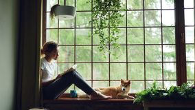 Het aantrekkelijke meisje in vrijetijdskleding leest blootvoets boekzitting die op venstervensterbank dichtbij aanbiddelijke huis stock footage