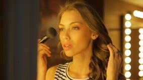 Het aantrekkelijke meisje zit in een zaal, zettend make-uppoeder op haar gezicht met een borstel stock video