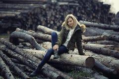 Het aantrekkelijke meisje zit op een boomboomstammen breng de ochtend in de tuin door, bekijkend de camera Royalty-vrije Stock Afbeelding