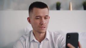 Het aantrekkelijke mens cellulair gebruiken en het maken van online praatje stock video