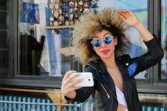 Het aantrekkelijke mooie modieuze jonge meisje neemt selfie stock afbeeldingen