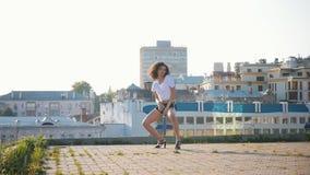 Het aantrekkelijke mulat jonge vrouw sexy dansen op hoge hielen op het dak stock video