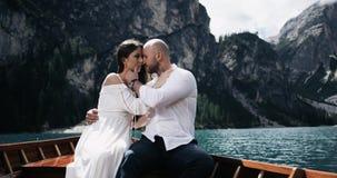 Het aantrekkelijke paar in de houten boot in het midden van meer het spelen met elkaar, mens raakt met liefde en stock video