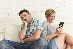 Het aantrekkelijke paar gaat liggen thuis de gelukkige verslaafde die van vrouweninternet op mobiele telefoon droevige echtgenoot Royalty-vrije Stock Foto