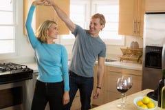 Het aantrekkelijke paar op een huisdatum die en pret in de keuken hebben heeft sterke chemie dansen stock afbeeldingen
