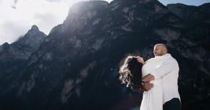 Het aantrekkelijke paar op het midden van verbazende landschap het glimlachen het besteden tijd samen, de man is draaien zijn mei stock footage