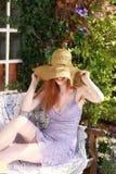 Het aantrekkelijke rode haired vrouw ontspannen in tuin royalty-vrije stock fotografie