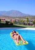 Het aantrekkelijke slanke jonge vrouw liggen op opblaasbaar sunbed op swimmi Stock Foto