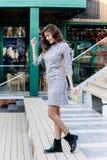 Het aantrekkelijke slanke modieuze meisje gekleed in een gebreide grijze kleding loopt onderaan de treden in de straat royalty-vrije stock afbeeldingen