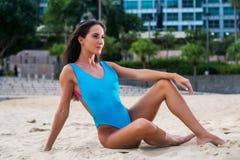 Het aantrekkelijke slanke swimwear model stellen op zand met toevluchthotel op de achtergrond Stock Afbeelding