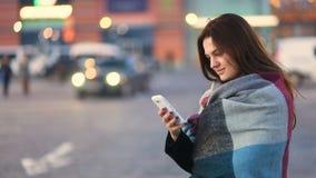 Het aantrekkelijke slimme vrij jonge mooie meisje die de telefoon onttrekken en in de stedelijke straat glimlachen met unfocused  stock video