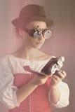 Het aantrekkelijke steampunkmeisje houdt de camera stock afbeeldingen