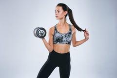 Het aantrekkelijke sterke gewicht van de vrouwenholding in haar die hand en het stellen in sportslijtage over grijze achtergrond  Royalty-vrije Stock Foto