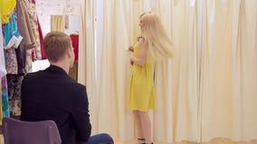 Het aantrekkelijke volwassen meisje met glimlach toont gele kleding aan de kerel in kleedkamer