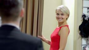 Het aantrekkelijke volwassen meisje met glimlach toont rode kleding aan de kerel in kleedkamer stock videobeelden