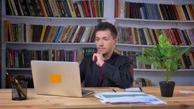 Het aantrekkelijke volwassen mens typen op de laptop zitting in het bibliotheekbureau die zijn gezicht draaien aan camera en het  stock video