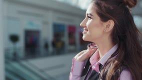 Het aantrekkelijke vrolijke meisje in het roze overhemd en het zwarte sleeveless jasje glimlacht en cirkels gelukkig in het winke stock footage