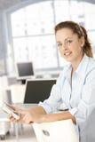 Het aantrekkelijke vrouw gebruiken mobiel in bureau het glimlachen Stock Afbeelding