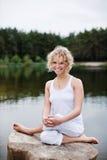 Het aantrekkelijke vrouw mediteren door nog water Stock Fotografie