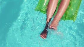 Het aantrekkelijke vrouw ontspannen op lilo bewegende voeten stock footage