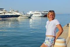 Het aantrekkelijke vrouw ontspannen op strandboulevard Mooi meisje die dichtbij zeehaven rusten stock afbeelding