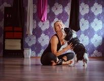Het aantrekkelijke vrouw spelen met haar leuke hond terwijl het zitten op vloer in de club van de yogageschiktheid royalty-vrije stock afbeeldingen