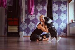 Het aantrekkelijke vrouw spelen met haar leuke hond terwijl het zitten op vloer in de club van de yogageschiktheid royalty-vrije stock fotografie