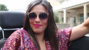 Het aantrekkelijke vrouw stellen bij de achterbank van convertibel stock footage