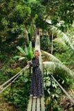 het aantrekkelijke vrouw stellen op hangbrug in wildernis stock foto's