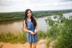 Het aantrekkelijke vrouw stellen tegen de achtergrond van bos Stock Foto's