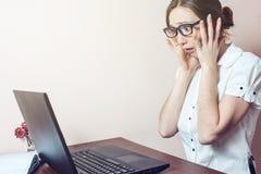 Het aantrekkelijke vrouw werken op kantoor met laptop grijpt zijn hoofd Stock Foto