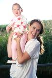Het aantrekkelijke vrouwelijke glimlachen met gelukkige baby Stock Afbeeldingen