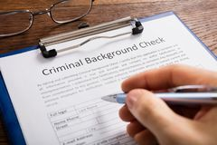 Het Aanvraagformulier van Person Filling Criminal Background Check stock afbeelding