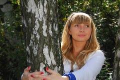 Het aardige blonde meisje en de berk Stock Foto