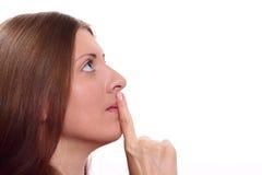 Het aardige meisje met een wijsvinger drukte aan lippen Royalty-vrije Stock Afbeelding