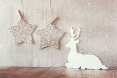 Het abstracte beeld van wit houten rendier en schittert sterren die op kabel hangen over schittert zilveren achtergrond Stock Foto