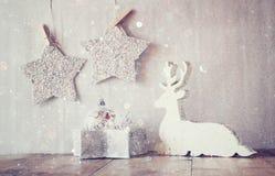 Het abstracte beeld van wit houten rendier en schittert sterren die op kabel hangen over schittert zilveren achtergrond Gefiltree Royalty-vrije Stock Foto