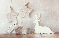 Het abstracte beeld van wit houten rendier en schittert sterren die op kabel hangen over schittert zilveren achtergrond Gefiltree Royalty-vrije Stock Foto's