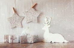 Het abstracte beeld van wit houten rendier en schittert sterren die op kabel hangen over schittert zilveren achtergrond Gefiltree Royalty-vrije Stock Afbeeldingen