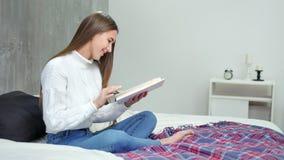 Het abstraherende jonge vrouwelijke handboek van de studentenlezing en het glimlachen op bed thuis volledig schot stock video