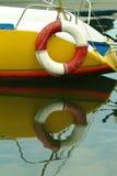Het achter deel van een boot met het levensring maakte, aardige waterbezinningen vast Stock Afbeeldingen