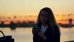 Het achter leunen tegen de omheining van de rivierdijk Zonsondergang in de stad Langzame Motie stock video