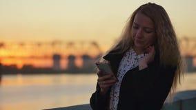Het achter leunen tegen de omheining van de rivierdijk Zonsondergang in de stad Langzame Motie stock videobeelden