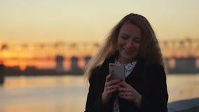 Het achter leunen tegen de omheining van de rivierdijk Zonsondergang in de stad Langzame Motie stock footage