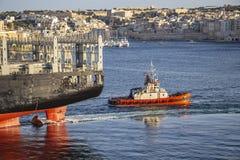Het achterdeel van een containerschip met een sleepboot bij Kalkara-Kreek, Grote Haven, Malta stock afbeeldingen