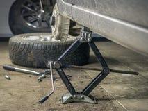 Het achtergedeelte van de auto in de garage met het verwijderde wiel Stock Afbeeldingen