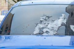 Het achterglas van de auto met sneeuwresidu's die tijdens de dooi van de winter smolten royalty-vrije stock afbeeldingen